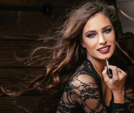 lapiz labial: belleza sonriente rica en encaje con l�piz labial de color rojo oscuro, el pelo del vuelo de cerca