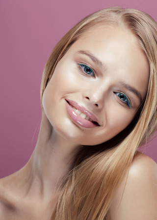 barbie: young pretty blonde woman with hairstyle close up and makeup on pink background smiling