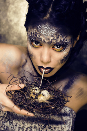 animal sex: fashion portrait of pretty young woman with creative make up like a snake, halloween Stock Photo