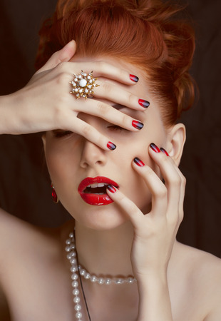 beauty stylish redhead woman with hairstyle and manicure wearing jewelry photo