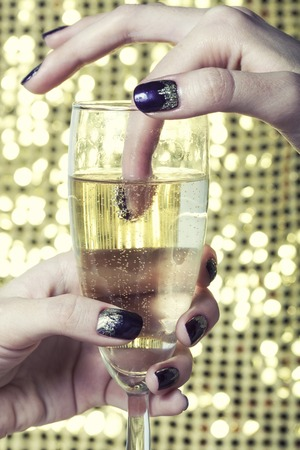beauty close up photo  fingers with creative manicure holding glass of champagne on gold background photo