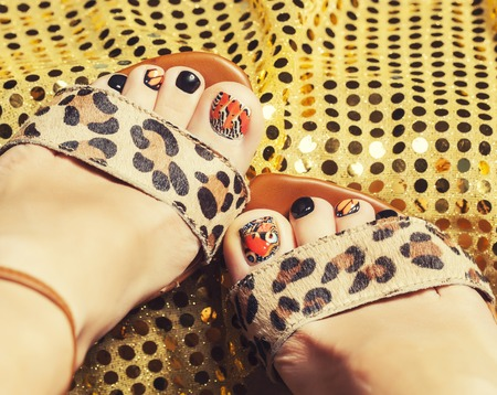 photo of pedicure like butterfly design on gold background close up photo