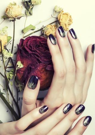 冬脱水乾燥花赤いバラとマニキュア爪の写真を閉じる