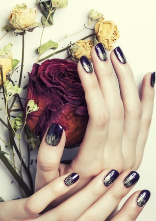 close up picture of manicure nails with dry flower red rose, dehydrated by winter