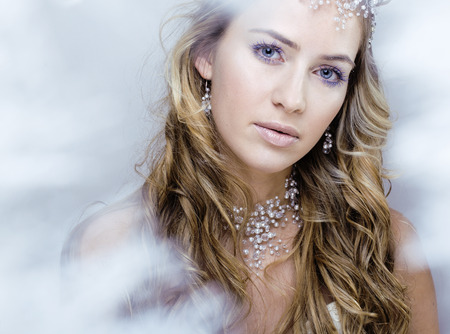 head close up: beauty young snow queen in fairy flashes with hair crown on her head close up