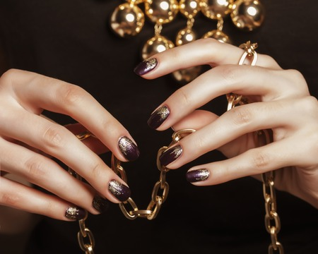 gold jewellery: close up photo hands with gold manicure holding chain on black