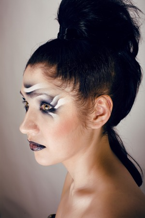zebra face: beauty young woman with creative make up like zebra closeup, waves on face