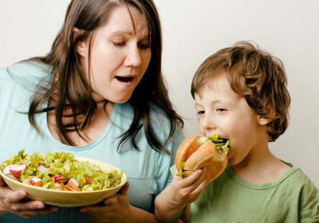 fat woman holding salad and little cute boy with hamburger teasing real family photo