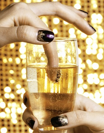beauty close up photo fingers with creative manicure holding glass of champagne on gold background, celebration stuff
