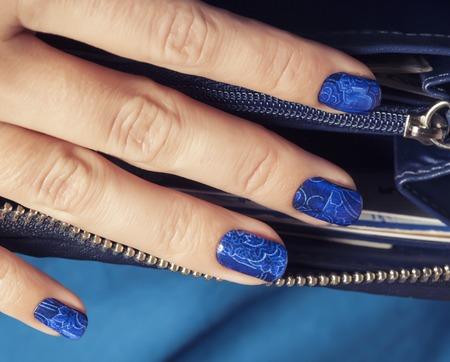 かなり指ディープ ブルーのマニキュアは、豪華なデザインの財布でクローズ アップ 写真素材