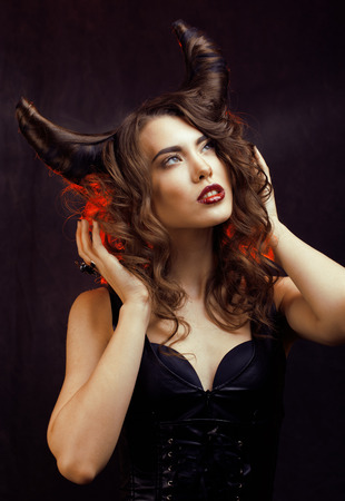 bright mysterious woman with horn hair, halloween celebration close up photo
