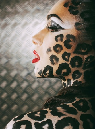 sexy halloween girl: young sexy woman with leopard make up all over body, cat bodyart closeup