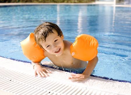 handcarves: little cute boy in swimming pool wearing orange handcarves