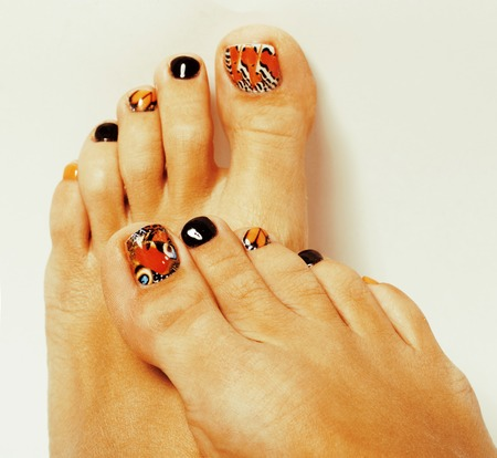 photo of pedicure like butterfly design on white background close up photo