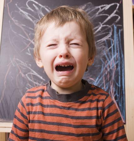 小さなかわいい男の子叫び、黒板の近くの学校で泣いて.