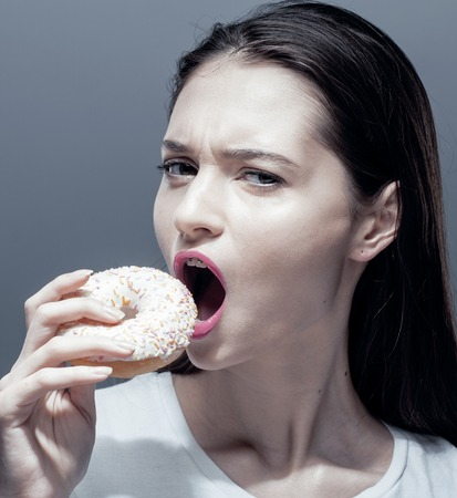 habbit: young pretty thin girl with donut close up, unhealthy habbit Stock Photo
