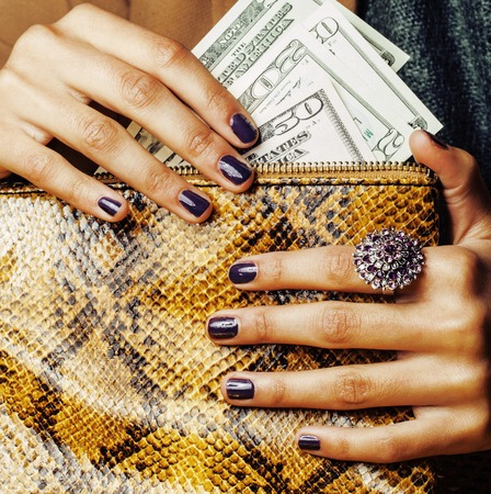 pretty fingers of african american woman holding money close up with purse, luxury jewellery on python clutch, cash for gifts