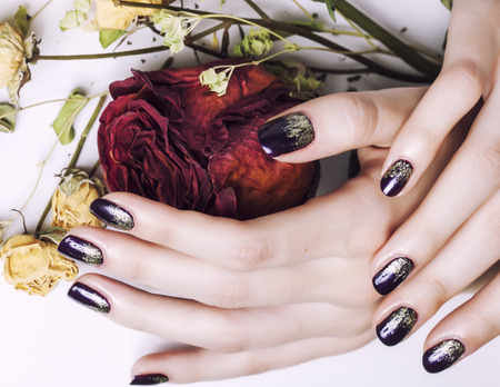 close up picture of manicure nails with dry flower red rose, dehydrated by winter close up photo