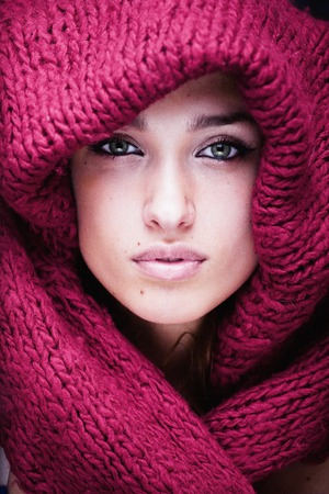 face close up: young pretty woman in sweater and scarf all over her face close up, real fashion girl