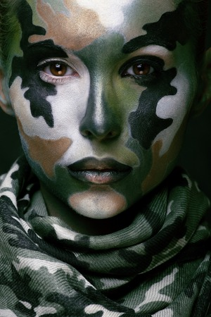 khaki: Beautiful young fashion woman with military style clothing and face paint make-up, khaki colors, halloween celebration close up