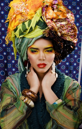 beauty bright woman with creative make up, many shawls on head like cubian, ethno look close up photo