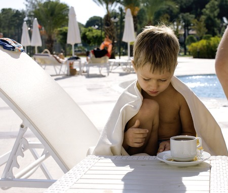 little  cute boy at swimming pool warmed up with towel and hot tea, hotel background