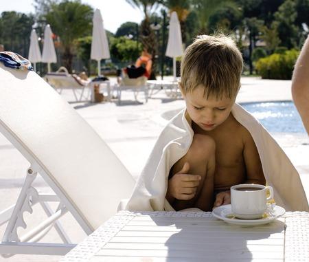 persona triste: peque�o muchacho lindo en la piscina calentada con la toalla y t� caliente, fondo del hotel Foto de archivo