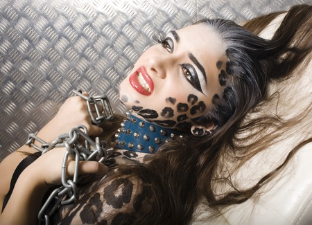 young sexy woman with leopard make up all over body, cat bodyart closeup, depression photo