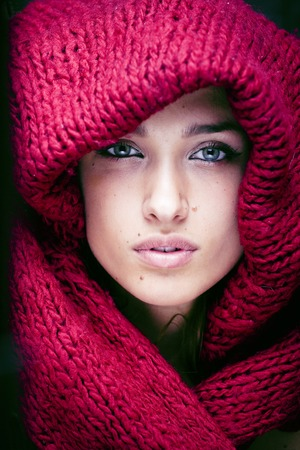 face close up: young pretty woman in sweater and scarf all over her face close up, real beauty