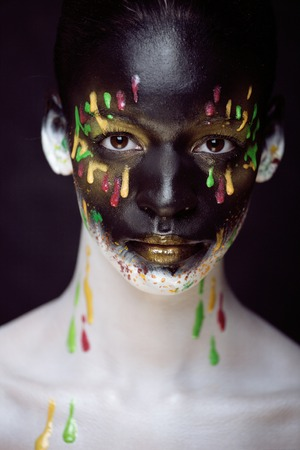 woman with creative make up close up, splashes of color on black face photo