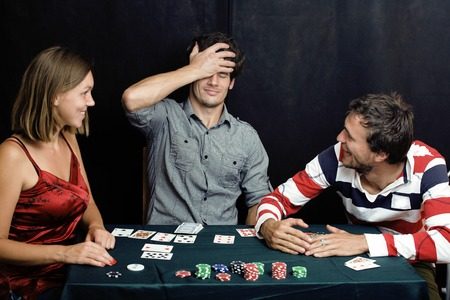 young real people playing poker, having fun photo