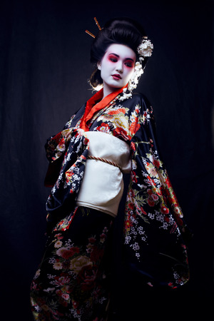 Young beautiful asian womans portrait, geisha in kimono on black, oriental style