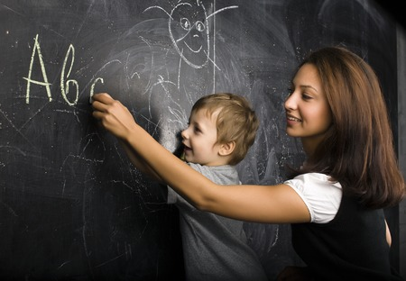 teaching adult: little cute boy with teacher in classroom smiling at blackboard
