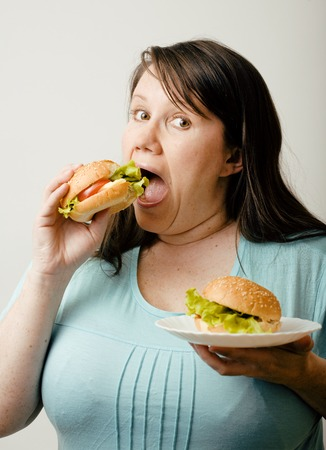 obsessive: fat white woman having choice between hamburger and salad on white