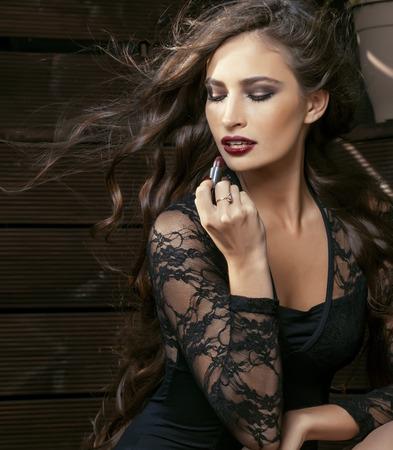 rijke vrouw: schoonheid glimlachende rijke vrouw in kant met donker rode lippenstift, vliegen haar close-up