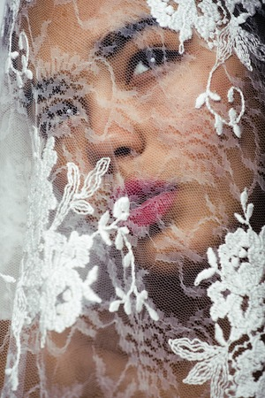 lace like: portrait of beauty young afro woman through white lace, like new bride under veil close up Stock Photo