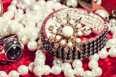 perls: lot of jewellery close up in red velvet box, ring bracelet with perl