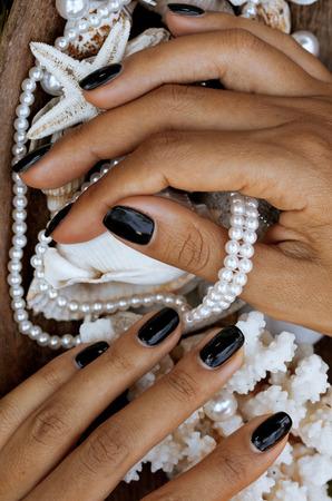 Nahaufnahme Nägel mit Maniküre zwischen Meer stuff, Shell, Korallen, Seesterne, afrikanische gebräunte Hände Standard-Bild - 37622866