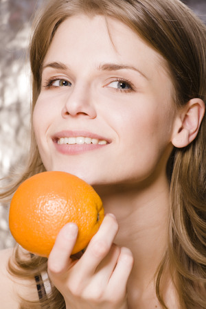 desires 25: young pretty woman with orange close up smiling