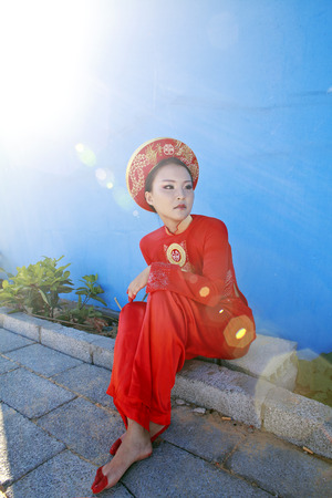 normal school: beauty young vietnamese woman in red national ethnic costume, real cheerful girl