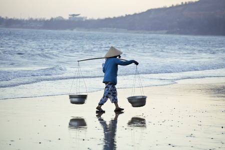 conical hat: vietnam woman in vietnamese hat walking on seacost at sunset, blue colored Stock Photo