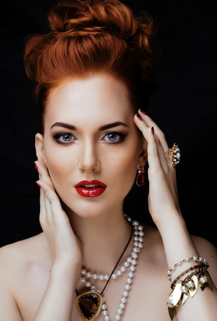 Beauty stylish redhead woman with hairstyle and manicure wearing jewelry pearl close up photo