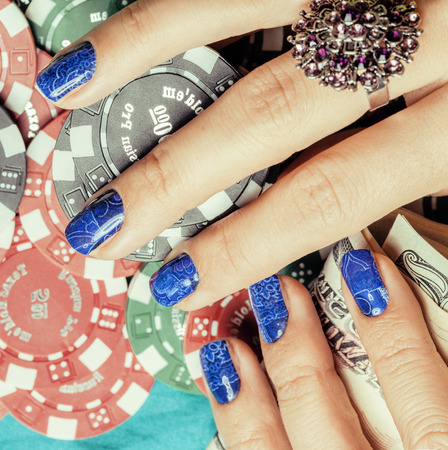 looser: Hands of young caucasian woman with blue manicure at casino table close up, deep indigo design on nails