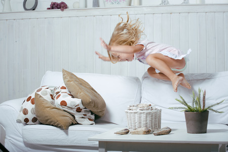 Little cute blonde norwegian real girl playing at home with pillows flying