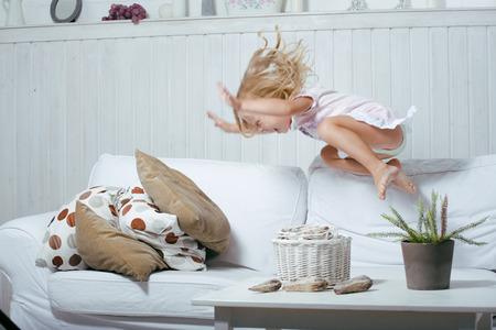 cuarto desordenado: Pequeña muchacha rubia verdadera noruego lindo que juega en casa con almohadas volar Foto de archivo