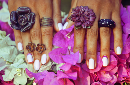 bright colorfull shot of african tanned hands with manicure among pink flowers wearing jewellery among flowers Standard-Bild
