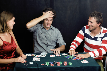 poker: young people playing poker on black background Stock Photo