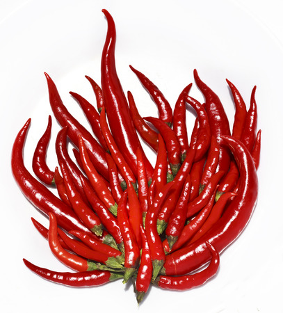 flame like: hot chili pepper like a burning flame fire isolated on white, close up shape Stock Photo