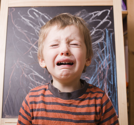 little cute boy screaming and crying at school near blackboard close up
