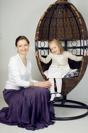 Portrait of mother and daughter at home, happy family in chair photo